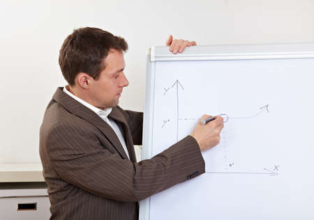 convince: Business man in office drawing strategy diagramm on flipchart