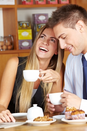 Happy woman sitting with man in café drinking a cup of coffee photo