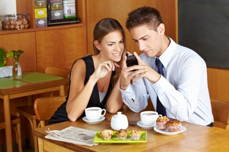 merchant: Business people in café with smartphone having a meeting Stock Photo