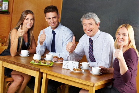 Four happy business people holding their thumbs up in a cafe, Stock Photo - 14333763