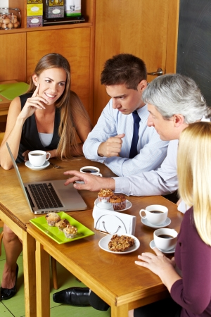 Happy business people having a meeting with laptop in a café photo