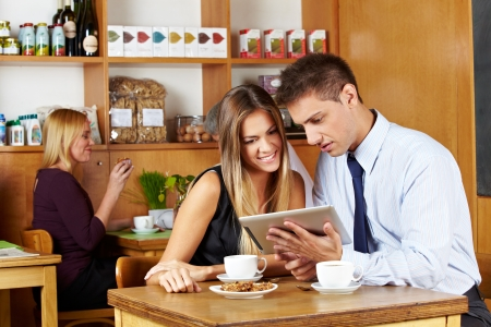 Business couple looking together at tablet computer in a café