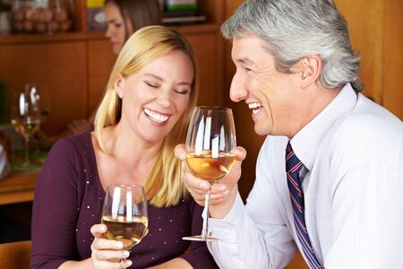 Happy senior couple drinking white wine in a restaurant photo