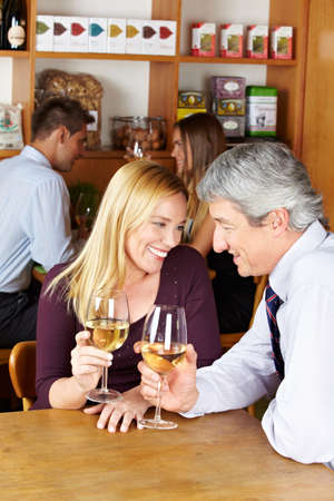 Elderly happy couple sitting with glass of white wine in a café Stock Photo - 14333754