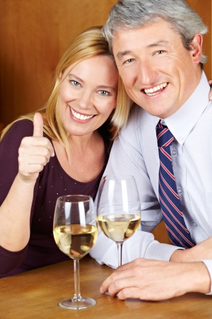 Woman of a happy senior couple in restaurant holding her thumb up Stock Photo - 14333745