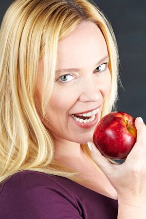 Attractive elderly woman eating a red apple photo
