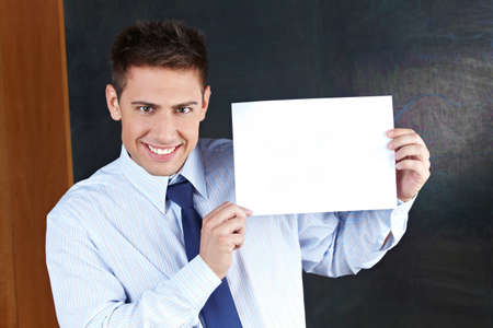Smiling teacher with empty white sign in front of chalkboard Stock Photo - 14333741