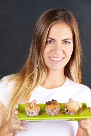 Happy attractive woman offering different muffins in a café photo