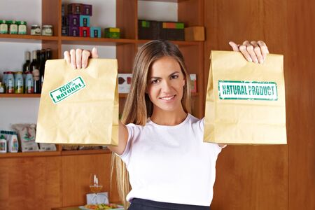 Happy smiling sales lady holding two paper bags in a store photo