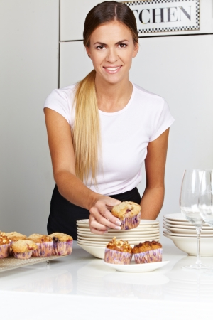 counter service: Smiling happy woman in catering firm serving muffins