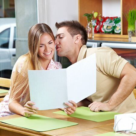 Young happy flirtive couple with menu in cafe, photo