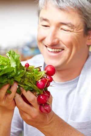 farm shop: Happy famer selling his radish in a farm shop Stock Photo