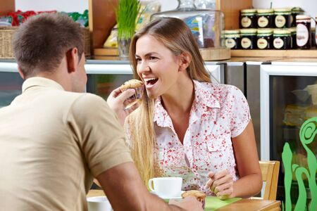 let out: Man in café giving woman a bite of his muffin