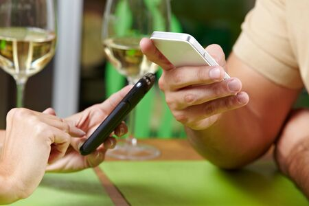 rude: Couple using their smartphones at the same time in a restaurant