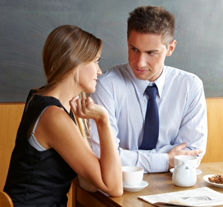 flirting women: Man and woman talking in a café while having a cup of coffee Stock Photo