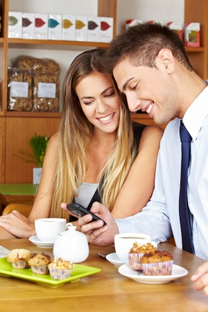 Smiling business couple with smartphone sitting in a café photo