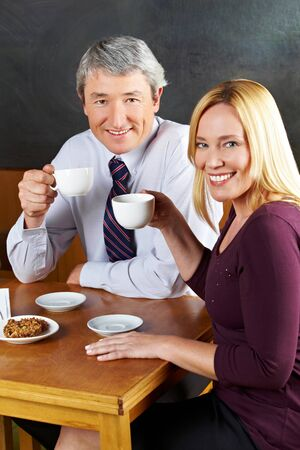 Elderly couple drinking coffee in café with smile on their face photo