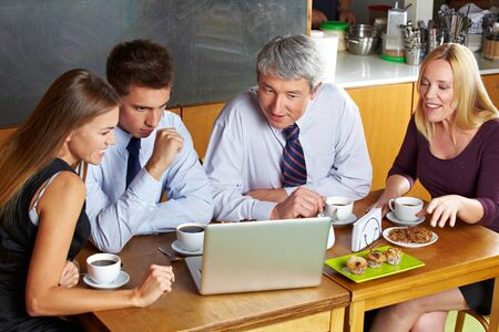 Business people looking at laptop in café during a meeting photo