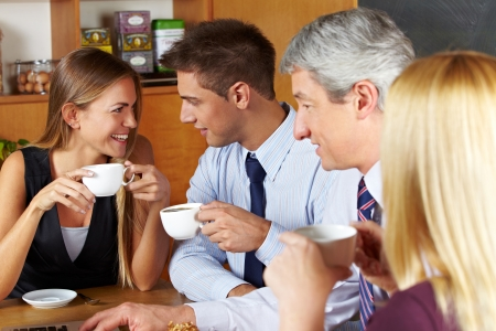 Four smiling business people taking a break with coffee in a café photo