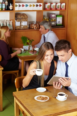 Happy couple sitting with a tablet computer in a café photo