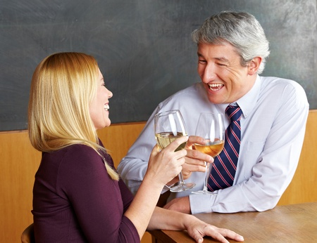 Happy senior couple raising their glasses for a toast in a restaurant photo