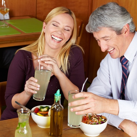 Smiling happy elderly couple having dinner in a restaurant photo