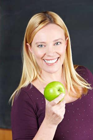 Smiling female teacher holding a green apple