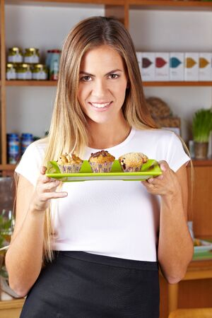 Attractive waitress in café serving different muffins photo