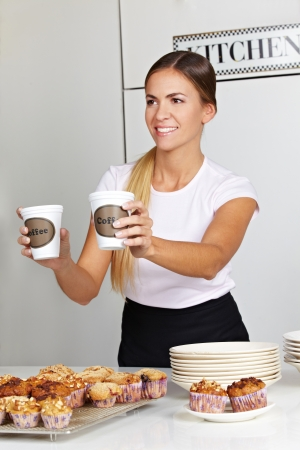 Happy woman selling cups of coffee in café behind counter photo