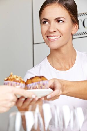 Female seller offering muffins in café behind counter photo