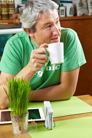 Man with tablet computer drinking cup of coffee in a café photo