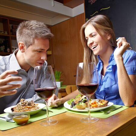 dinner date: Smiling happy young couple eating in a restaurant Stock Photo