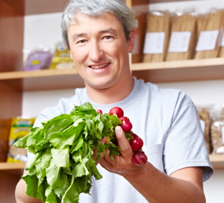 Senior farmer selling his vegetables in his farm shop photo