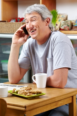 Smiling senior man making a call with his smartphone in a café photo