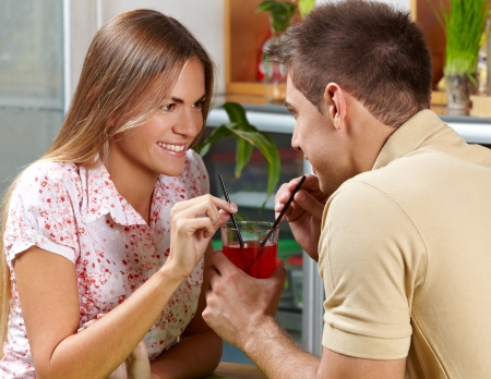 Happy young couple drinking cocktail with straws in a bar Stock Photo - 14364404