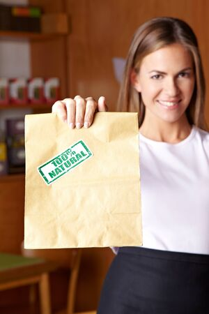 Young attractive woman holding paper bag in health food store photo
