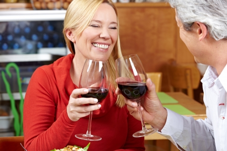 Elderly couple in restaurant cheering with red wine Stock Photo - 14364393