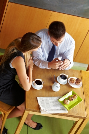 Two business people having a break in café and looking at a smartphone photo