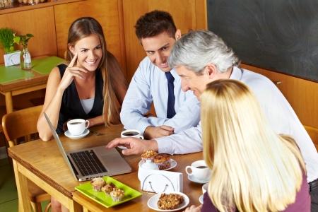 노트북 컴퓨터에서 찾고 카페에서 비즈니스 팀 회의 스톡 콘텐츠