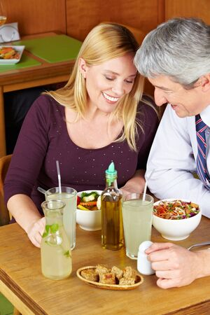 eat out: Two happy seniors having dinner in a restaurant