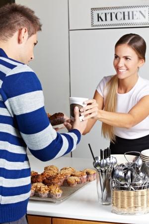 Klanten kopen koffie en muffins in cafe van lachende vrouw
