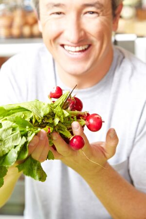 farm shop: Smiling farmer with a bunch of radish in the farm shop