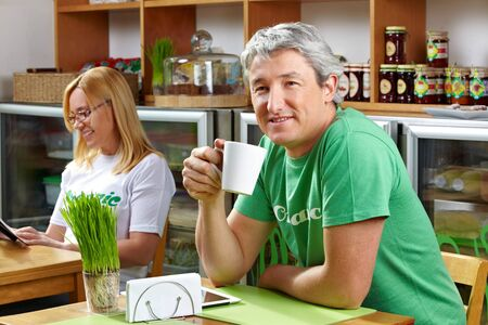 Smiling senior man drinking cup of coffee in a café photo