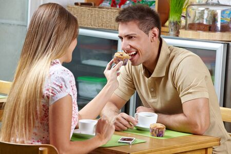 let out: Young woman letting man taste a muffin in a café