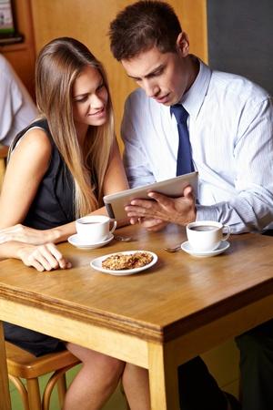 카페에서 태블릿 컴퓨터와 함께 작업하는 두 비즈니스 사람