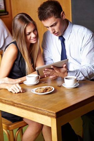 Two business people working with tablet computer in a café Stock Photo - 14428684