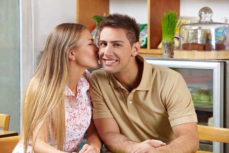 Attractive woman kissing smiling man on cheek in a café photo