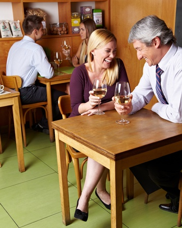 Two happy laughing senior people drinking white wine in restaurant photo