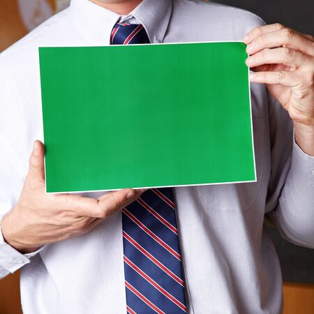 Manager holding empty green sign in front of his chest photo