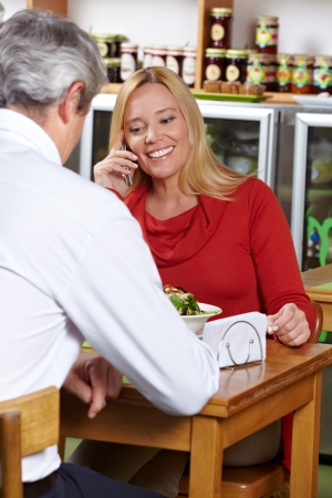 Elderly woman using her smartphone in a restaurant to make a call Stock Photo - 14428679